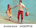 Couple walking on beach. Young happy married hipsters in trendy clothes playing and laughing on beach and holding their shoes. Sunny summer day. Outdoor shot - stock photo