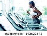 woman running on a treadmill at ... | Shutterstock . vector #142622548