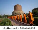 Small photo of Buddhist monks walking candlelit Or publish dharma at Dhamek Stupa at Sarnath near Varanasi or Madhya Pradesh India, the concept of travel incredible India.
