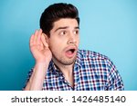 Small photo of Close up photo amazing he him his macho listen rumours chatterbox person show big interest hand arm palm near ear look empty space wear casual checkered plaid shirt isolated bright blue background