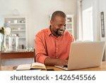 Smiling black man using laptop...
