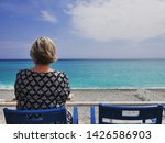 Oceanfront view, including woman looking out to sea in the foreground. Taken in Nice, France using a Panasonic GX85.
