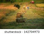 People Work In A Field Hay Bales