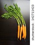 fresh carrots on a black wooden ... | Shutterstock . vector #142711423