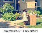 Small photo of retro girl wearing sunglasses with lemonade stand