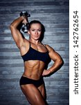 Woman bodybuilder with dumbbell on wall background. - stock photo