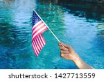 American flag waving in celebration with pool water in background.  Fourth of July or Memorial Day holiday concept.