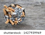 Small photo of Ashtray full of cigarettes butts close-up on wood background