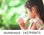 cute asian child girl drinking... | Shutterstock . vector #1427950673