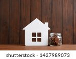 house model and jar with coins... | Shutterstock . vector #1427989073