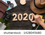 Small photo of 2020 new year eve trip.top view hand putting happy new year number on wood table with adventure accessory item,holiday vacation resolutions planning