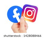 Small photo of Kiev, Ukraine - May 15, 2019: Hand holds new Facebook logo and Instagram printed on paper. Instagram is a photo and video-sharing social networking service owned by Facebook.