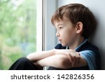 Sad Child Sitting On Window