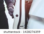 Close up hand pulling the handle of a car thief  wearing black clothes and glove stealing automobile trying door handle to see if vehicle is unlocked  trying to break into. car theft concept. - stock photo
