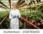 Portrait of happy female biologist standing in a plant nursery and looking at camera.