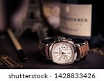 Small photo of 18 June 2019.Close-up macro detail of Patek Philippe luxury Swiss watch on art book around by a tiny tower and bottle