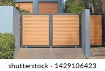 Small photo of Automatic swing open front gates with horizontal wooden slats