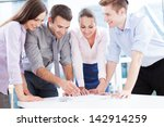 coworkers leaning over table in ... | Shutterstock . vector #142914259