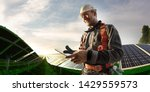 Solar energy engineer using tablet for check power station  - stock photo