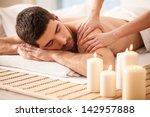 young man enjoying a massage. | Shutterstock . vector #142957888