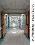 Small photo of Landstuhl, Germany - May 13, 2019: An empty, well-lit hallway in a hospital with doors leading off to either side.
