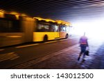 driving bus and walking person in a bridge underpass in motion blur - stock photo