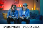 Small photo of Excited Black Gamer Girl and Young Man Sitting on a Couch and Playing Video Games on Console. They Plays with Wireless Controllers. Cozy Room is Lit with Warm and Neon Light.