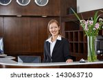 Stock photo happy female receptionist standing at hotel counter 143063710