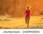 Sport, outdoor life and healthy lifestyle concept. Happy blonde woman running on seashore of El Matador Beach. Fitness girl jogging in sunset beach, California West Coast. Malibu coast, United States.
