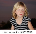 Head shot of young teen blond girl outdoors against the night sky - stock photo