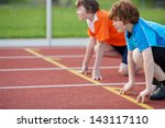Small photo of Side view of male runners on starting position at racetrack