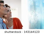 Stock photo happy couple looking at modern painting in art gallery 143164123