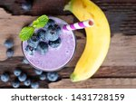 Small photo of Blueberry mix banana smoothie purple colorful fruit juice milkshake blend beverage healthy high protein the taste yummy In glass,drink episode morning on a wooden background from top view.