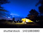 Family tent with rigid steel poles on camping ground under Starry sky with Milky Way - stock photo