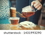 Stock photo hand of the waitress pours a cup of tea at the client s table close up of the glass teapot with 1431993290