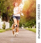 Stock photo happy young woman jogging with her beagle dog 143211553