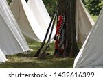 18th century Revolutionary War replica muskets and a redcoat jacket propped up against a tree in the middle of a campsite