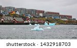Old colonial harbor with iceberg, colorful Nuuk city, capital of Greenland