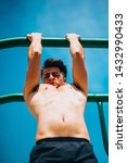 Small photo of Young man in sportswear doing pull ups on pull up bar in outdoors gym