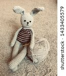 Stock photo knitted hare gray hare crocheted amigurumi on a gray background with a lying skein of 1433405579