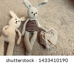 Stock photo knitted hare gray and white hare crocheted amigurumi on a gray background with a skein of 1433410190
