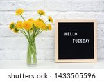 Small photo of Hello Tuesday words on black letter board and bouquet of yellow dandelions flowers on table against white brick wall. Concept Happy Tuesday. Template for postcard.
