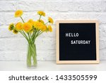 Small photo of Hello Saturday words on black letter board and bouquet of yellow dandelions flowers on table against white brick wall. Concept Happy Saturday. Template for postcard.