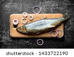 Stock photo salted herring on a wooden cutting board with onion rings on dark rustic background 1433722190