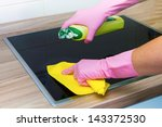 Closeup of female hands in protective gloves cleaning stove in the kitchen. - stock photo