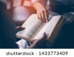 Small photo of Male adults are reading the Holy bible by pointing to the character and to share the gospel to youth. The cross symbol, The books of the Bible, Concepts of Christianity.