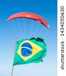 Small photo of Brazilian flag waving with a paraglider behind. Original humor and patrotism. Funny view background. Scene Red Parachute and wind in Brasil.