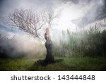 Weird female figure in black beckoning someone from the morning mist - stock photo