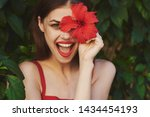 A Happy Woman With A Red Flowe...