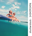 sister and brother sitting on... | Shutterstock . vector #1434592496
